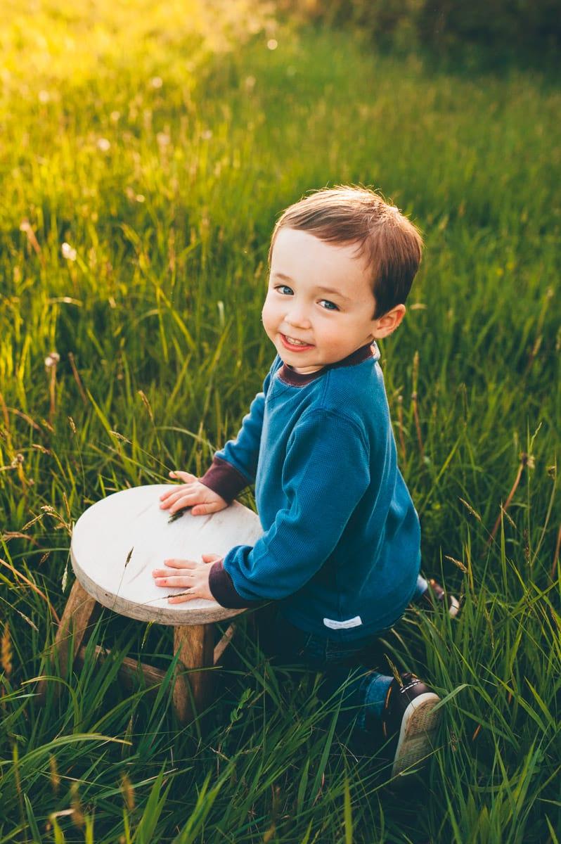 Little boy kneeling next to stool in grassy field.