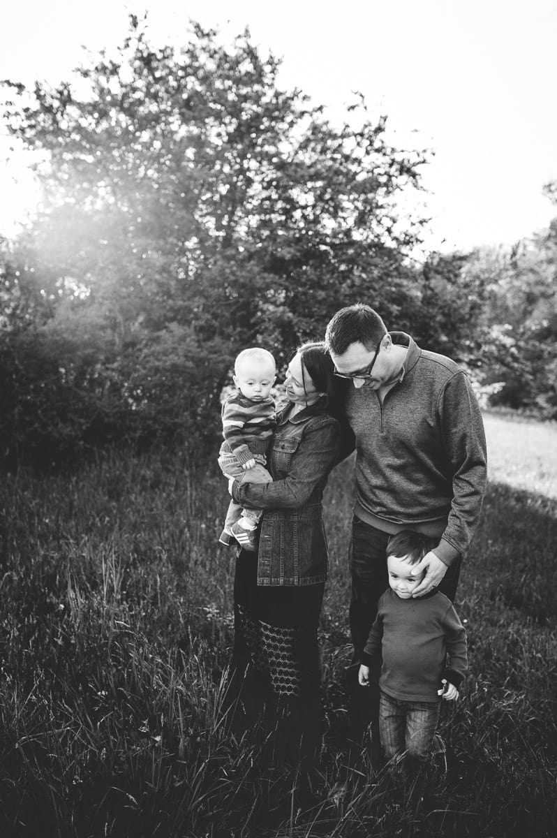 Black and white image of a family of four with two little boys in a Medina, OH field.