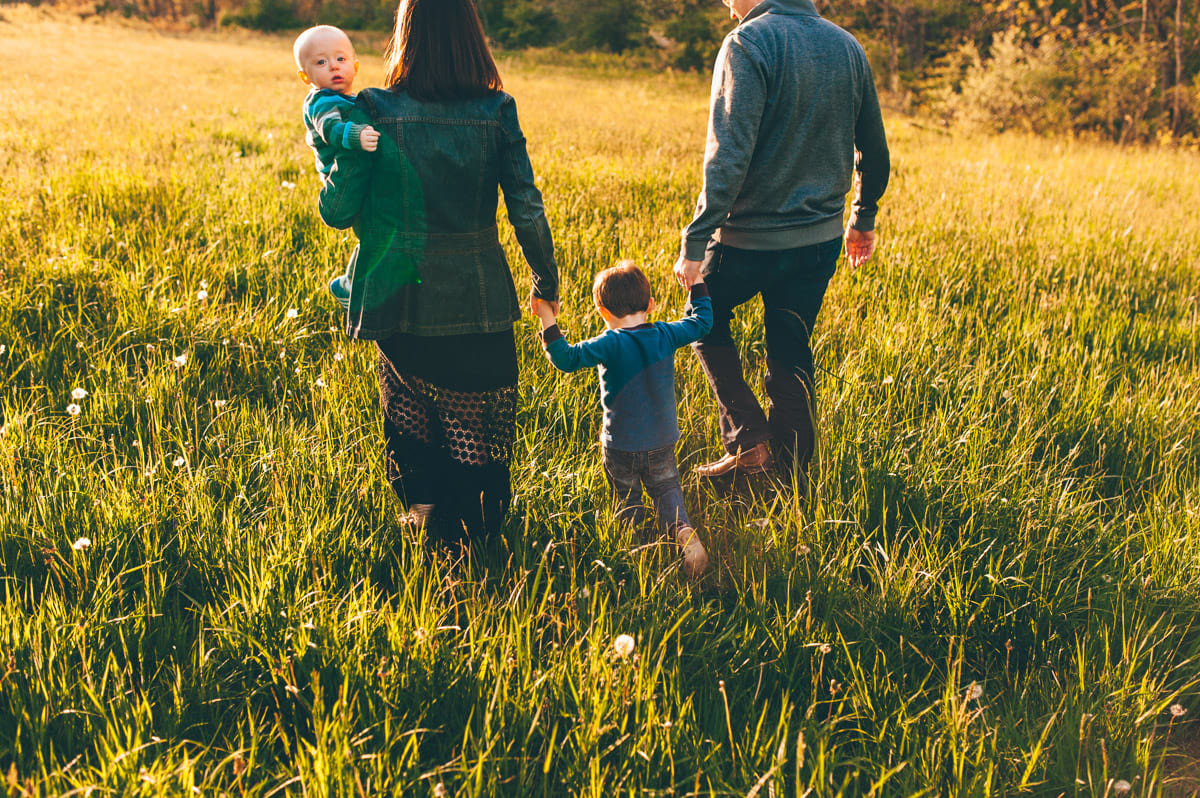 Family walking in the sunset through a field next to the Lodge at Allardale.