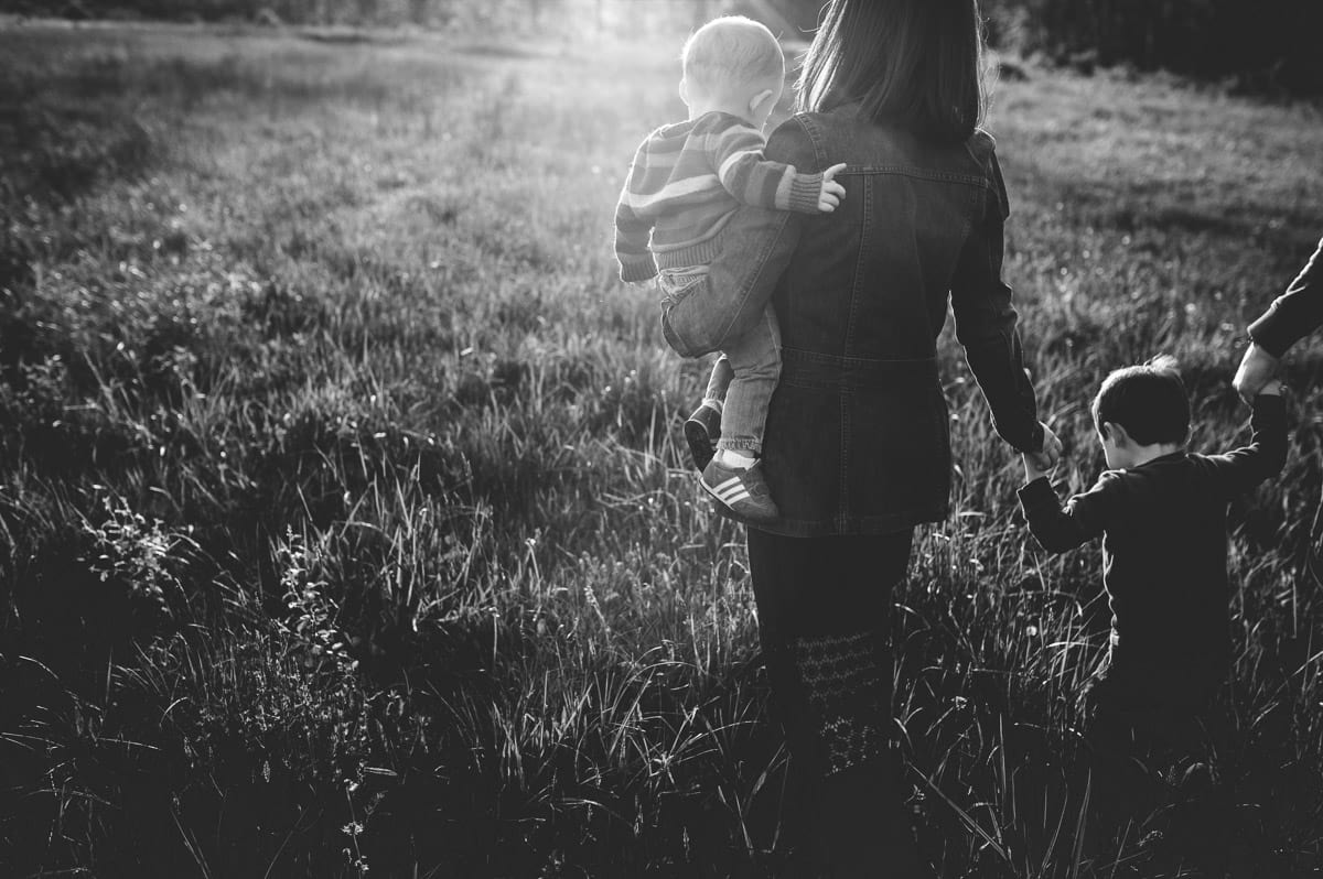 Mom carrying baby boy during sunset in a field near Allardale Park.