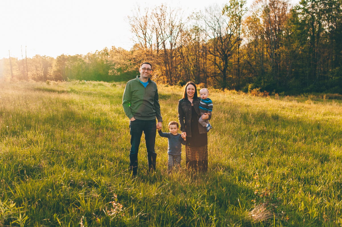 Family with mom, dad and two boys smiling for photos in a sunset field.