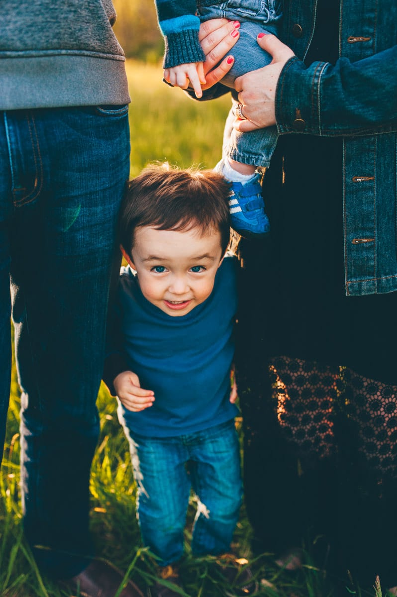 Little boy with brown hair peeking between parents during photo session.