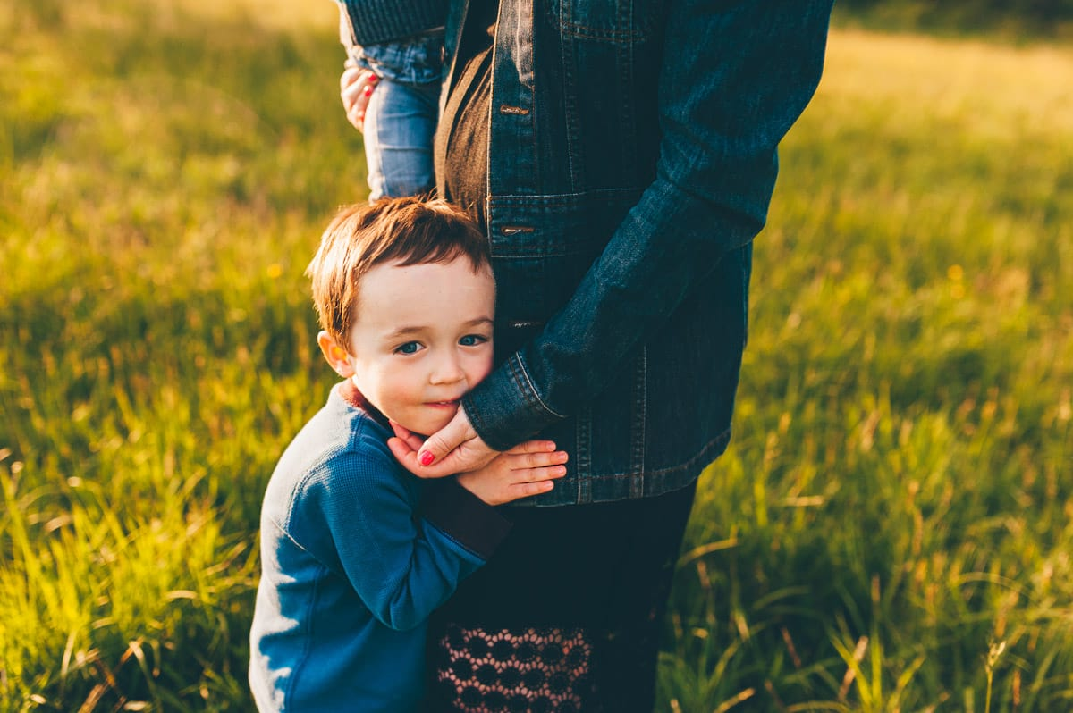 Sweet photo of mom sweetly placing hand on her son's face during photo session.