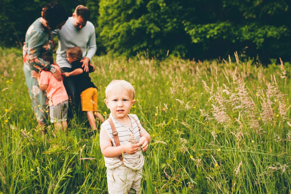 Blonde boy in suspenders in grassy field with family.