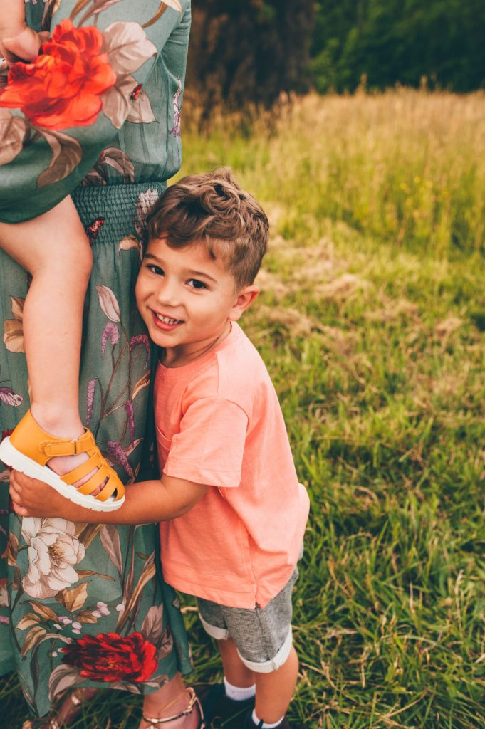 Boy hugging mom's leg during Medina family photo session at Allardale.