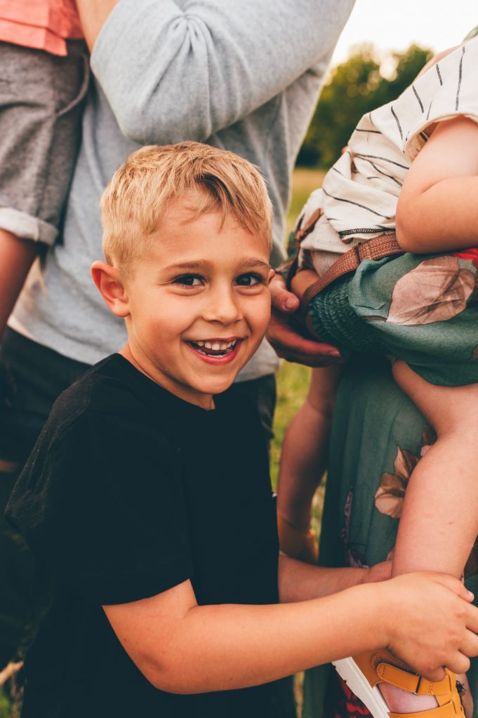 Blonde boy smiling at camera during family photo session in Medina.