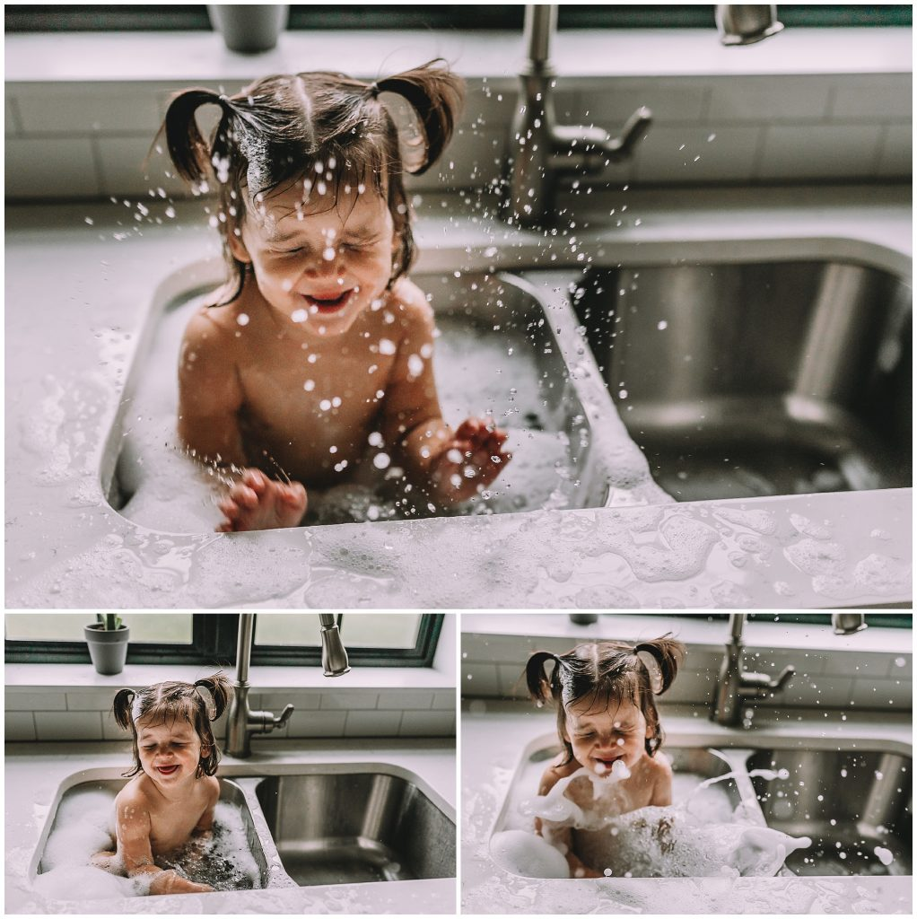 Funny baby girl having fun in sink bath.