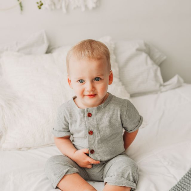 Little boy in gray romper on a white bed during photo shoot near Cleveland, OH.