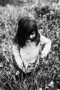 Black and white photo of little girl exploring flowers in a field near Akron, OH.