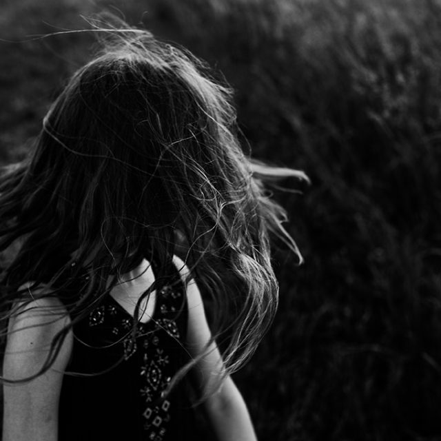 Black and white photo of little girl's hair in the wind.