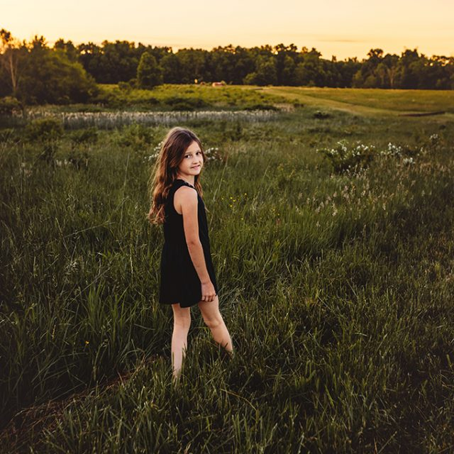 young girl walking in grassy field at sunset