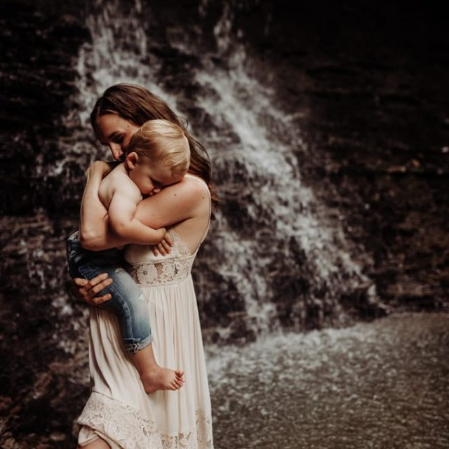 Mother holding son in water fall in Cuyahoga Valley National Park Blue Hen Falls.
