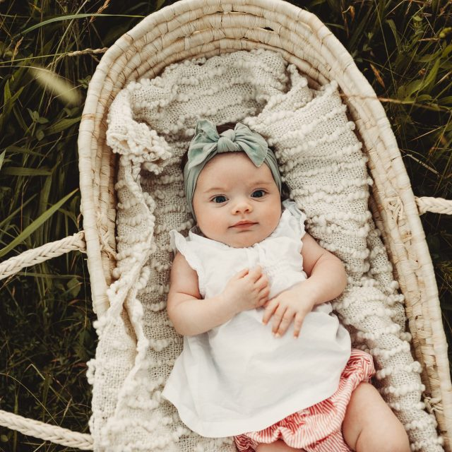 Adorable Newborn baby girl in a moses basket outdoors near Cleveland.