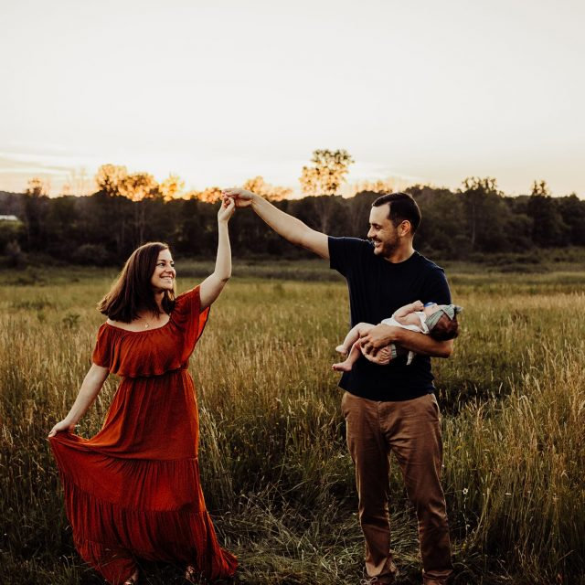 Young couple with newborn baby girl dancing together in grassy field at sunset.