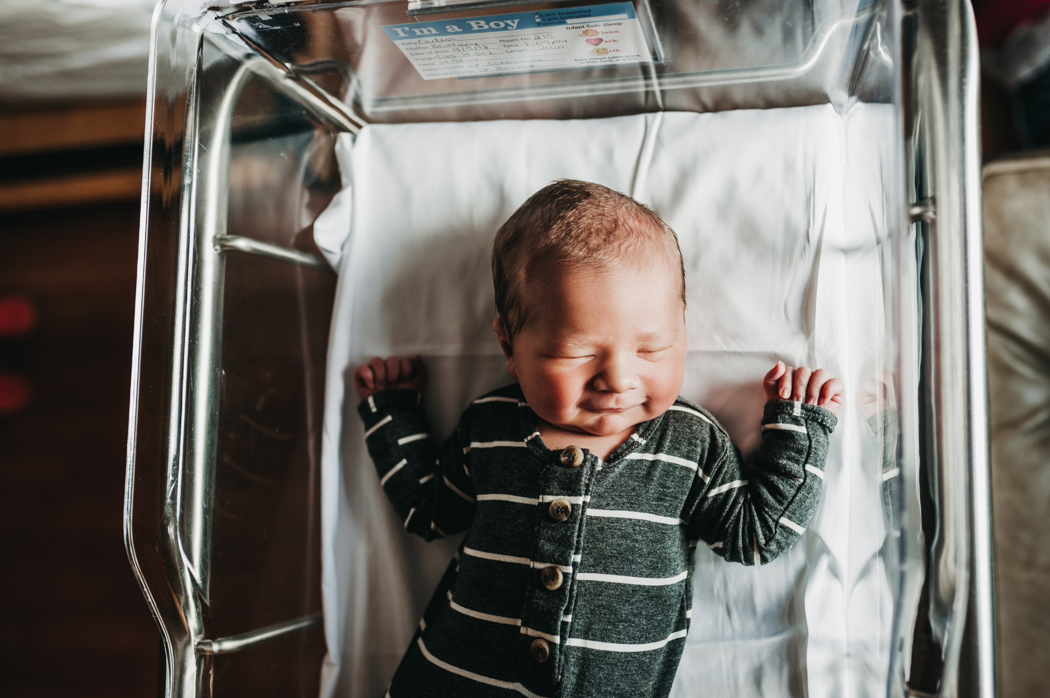 Newborn baby boy in Akron area hospital bassinet smiling in his sleep.