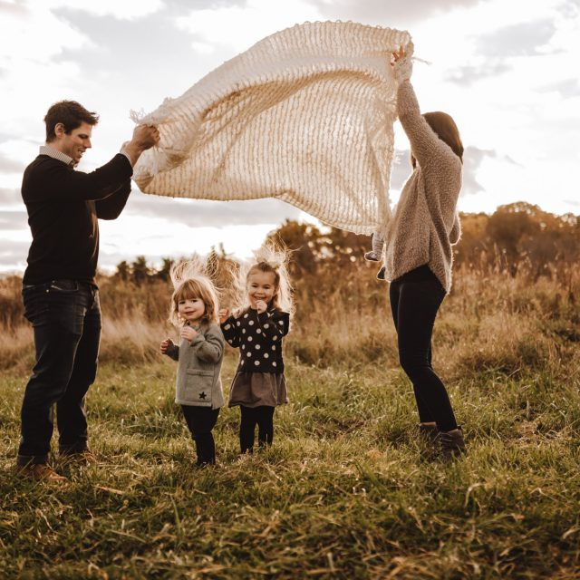 Boy and girl playing parachute with blanket with parents tossing blanket in the air.