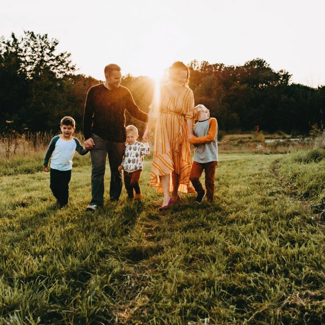 Family of five walking with sunset behind them in the grass in Medina, OH