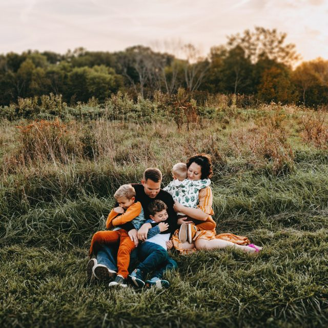 Family of five with young boys holding and snuggling during outdoor family photo session near Cleveland.