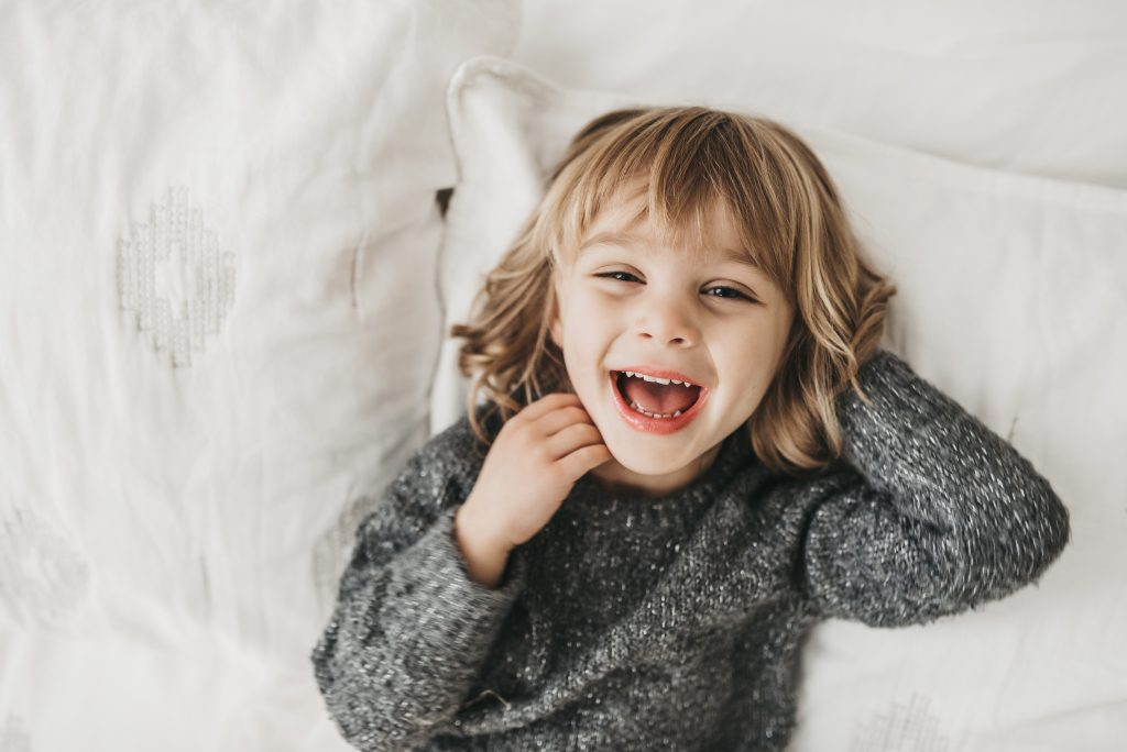 Little girl Arden laughing laying on white bed in Medina, OH studio.