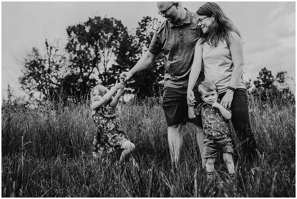 Black and white image of family in grassy field during photography session in Medina, OH.